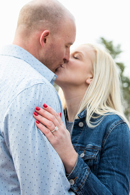 Couple kissing and showing engagement ring at Biltmore Estate in Asheville
