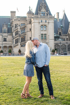 Couple kissing on the front lawn at Biltmore Estate in Asheville