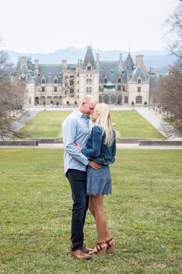 Couple touching foreheads on the esplanade at Biltmore Estate in Asheville during engagement photo shoot