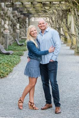 Couple under wisteria pergola at Biltmore Estate in Asheville during engagement photos