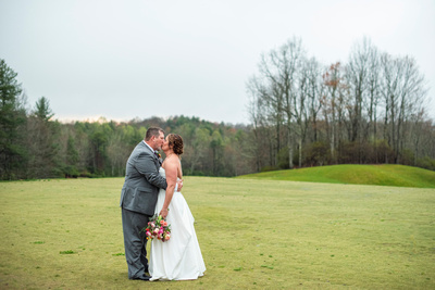 Bride and groom kissing on the green at Connestee Falls wedding