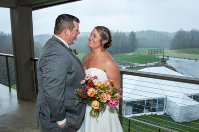 Bride and groom portrait on balcony during rainy day wedding at Connestee Falls