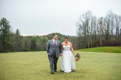 Bride and groom walking on the green at Connestee Falls wedding