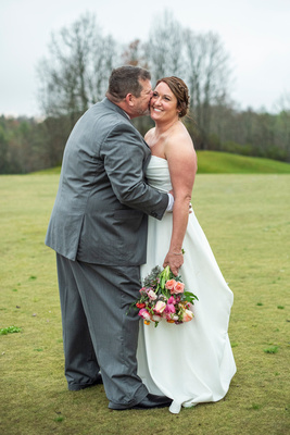 Grooom kissing bride on cheek at Connestee Falls wedding outside