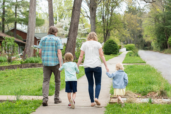 Asheville family holding hands and walking away from camera while on the sidewalk