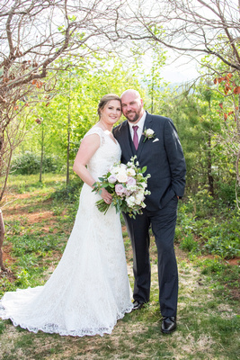 Bride and groom portrait under branch arch at Something Blue Mountain Venue in Marion NC
