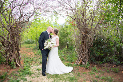 Wedding couple kissing under branch arch at Something Blue Mountain Venue near Asheville NC
