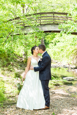 Bride and groom kissing next to creek at botanical gardens before wedding the Grand Bohemian Hotel in Asheville NC