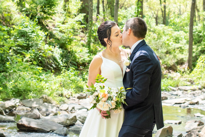 Couple kissing in the creek at botanical gardens before the Grand Bohemian Hotel in Asheville NC