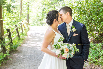 Wedding couple kissing on pathway at botanical gardens before wedding at the Grand Bohemian Hotel in Asheville NC