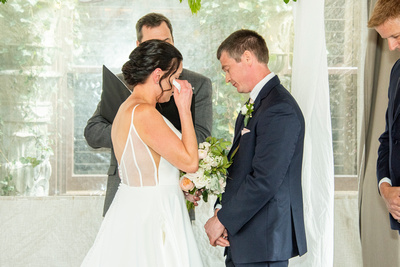 bride wiping away tear during ceremony at the Grand Bohemian Hotel in Asheville NC