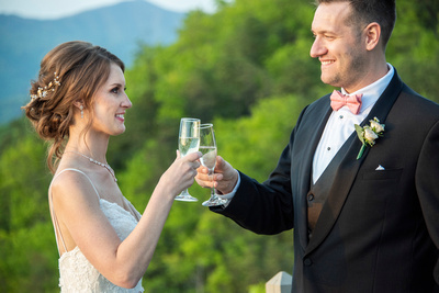 Bride and groom cheers champagne on mountain top at Hawkesdene in Andrews, NC