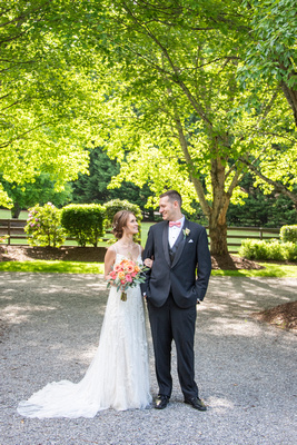 Bride and groom looking at each other while standing among tall trees at Hawkesdene in Andrews, NC