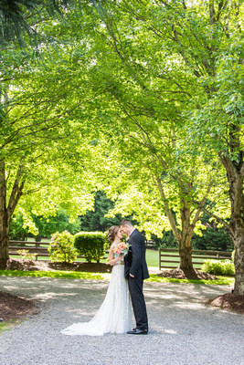 Bride and groom standing among trees at Hawkesdene in Andrews, NC