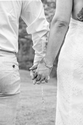Bride and grooms hands with rings and rosary at wedding at AirBnb in Burnsville NC near Asheville NC