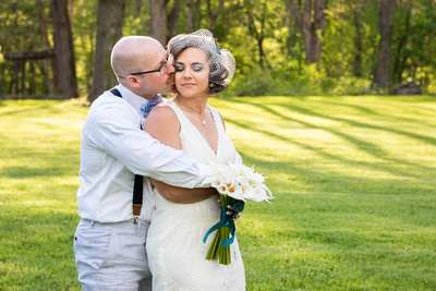 Groom kissing bride on cheek at wedding at AirBnb in Burnsville NC near Asheville NC