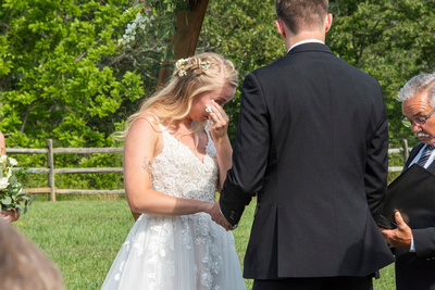 Bride wiping away tear during wedding ceremony at Claxton Farm in Weaverville, near Asheville, NC