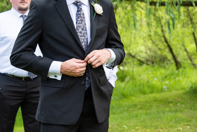 Groom buttoning jacket at wedding at Claxton Farm in Weaverville, near Asheville, NC