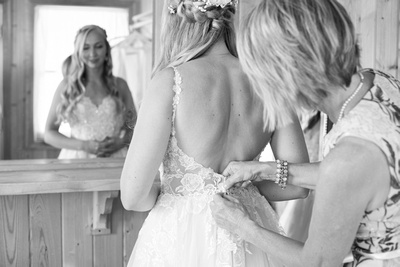 Mother of bride helping bride get in dress at Claxton Farm in Weaverville, near Asheville, NC