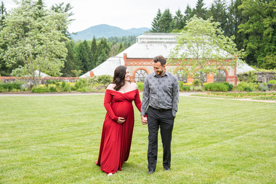 Couple walking through walled garden holding hands during maternity photos at Biltmore Estate in Asheville