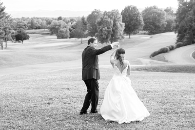 Bride and groom dancing on golf course at wedding at Omni Grove Park Inn Seely Pavilion