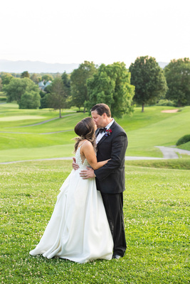 Bride and groom kissing at sunset at wedding at Omni Grove Park Inn Seely Pavilion