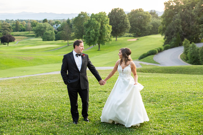 Bride and groom holding hands on golf course at wedding at Omni Grove Park Inn Seely Pavilion