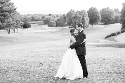 Bride and groom laughing on golf course at wedding at Omni Grove Park Inn Seely Pavilion