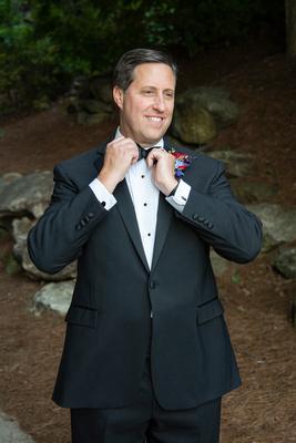 Groom straightening bow tie at wedding at Omni Grove Park Inn Seely Pavilion