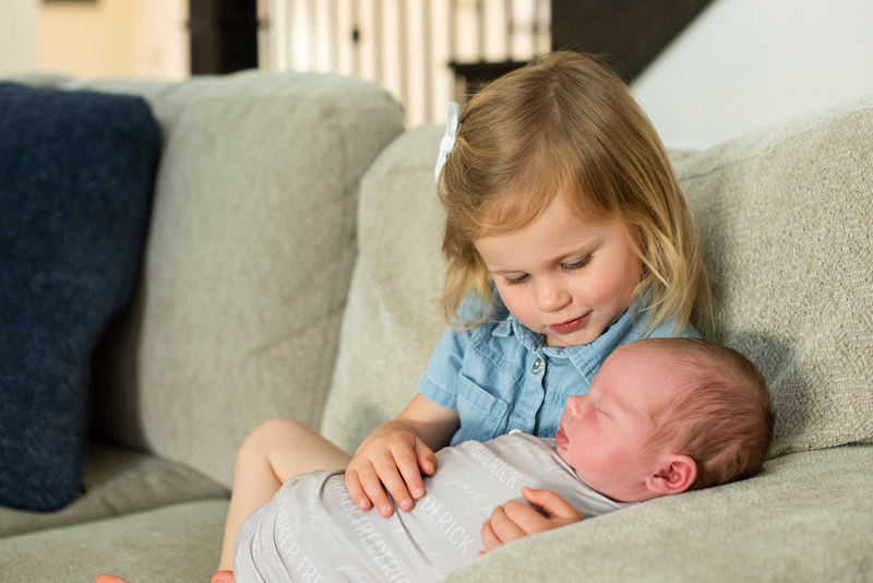 Asheville newborn photographer big sister holding baby brother