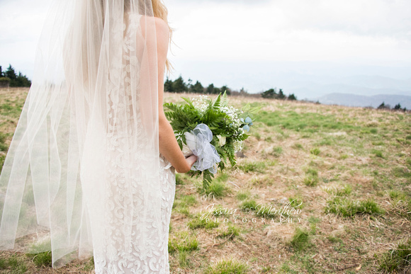lace bridal gown and mid length veil with bouquet on round bald in roan mountain