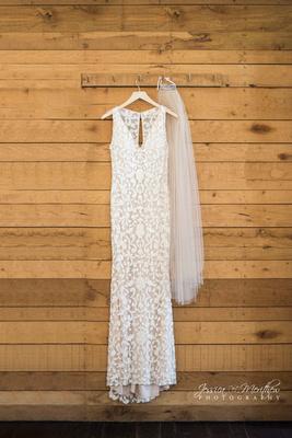 lace wedding dress hanging shiplap rustic