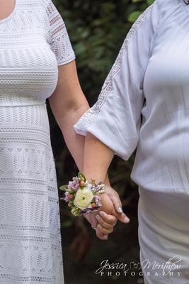 brides holding hands flower corsage