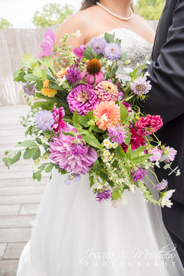 bride and groom holding wildflower bouquet at highland brewing wedding