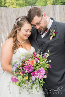 bride and groom touching forheads with wildflower wedding bouquet at highland brewing