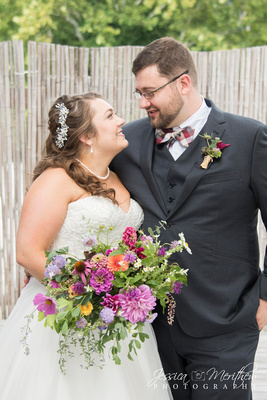 bride and groom with carolina flowers wildflower bouquet at highland brewing wedding rooftop