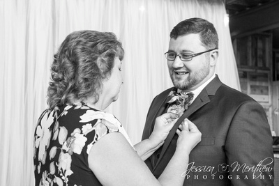 mother of the groom pinning boutonniere on groom in black and white