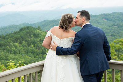 Bride and groom kissing and looking out at mountains at Hawkesdene wedding venue in Andrews NC near Asheville
