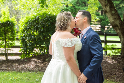 Bride and groom kissing during wedding first look at Hawkesdene wedding venue in Andrews NC near Asheville