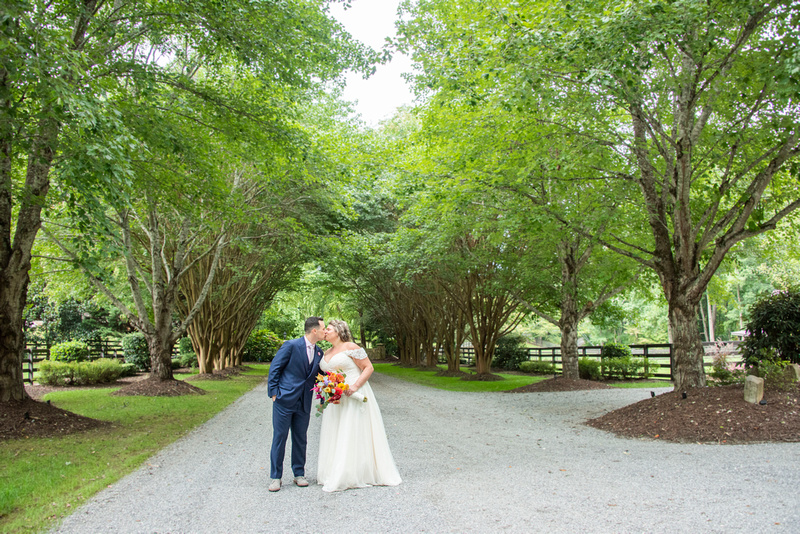 Bride and groom kissing under canopy of trees at Hawkesdene wedding venue in Andrews NC near Asheville