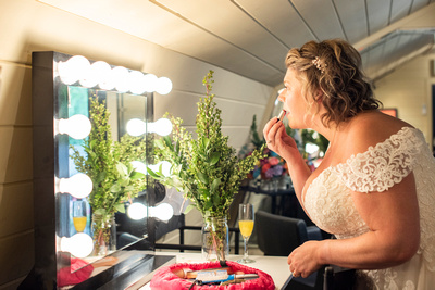 Bride putting on lipstick at Hawkesdene wedding venue in Andrews NC near Asheville