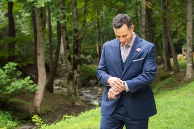 Groom adjusting watch at Hawkesdene wedding venue in Andrews NC near Asheville