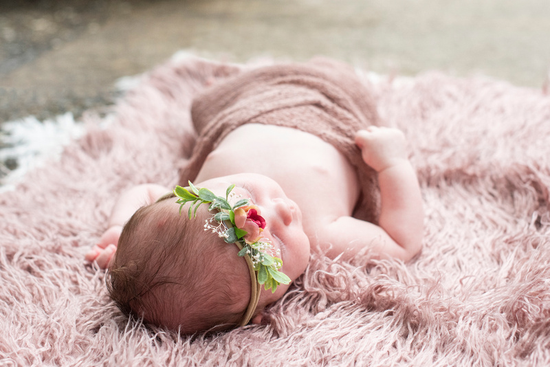 Newborn baby girl laying on blush rug at The NC Arboretum in Asheville