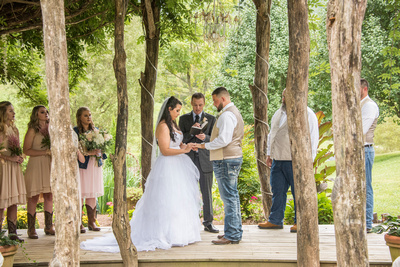 bride and groom exchanging rings at timber hall events