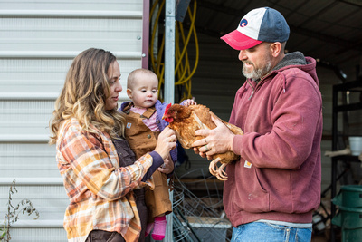Family petting chicken during farm photo shoot in Asheville