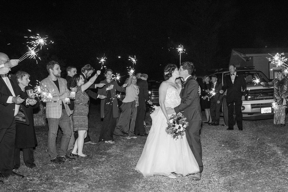 Bride and groom kissing during spakler exit at wedding