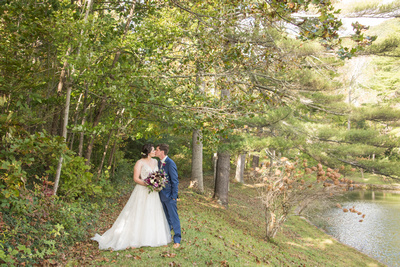 Wedding couple kissing next to pond at Bull Creek Ranch in Asheville