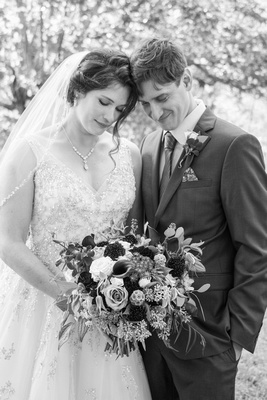 Wedding couple looking at bouquet in Asheville