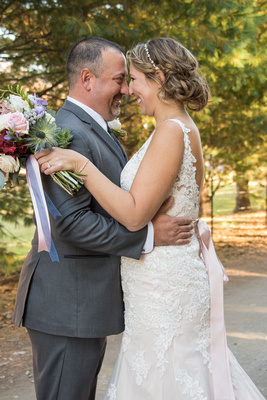 Bride and groom touching noses at Reflections at the Pond in Asheville
