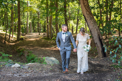 Bride and groom holding hands walking through forest at Highland Brewing Wedding in Asheville